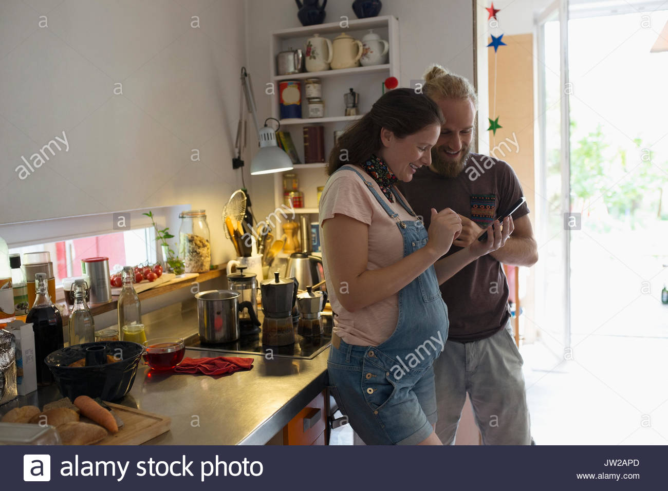 Pregnant couple using cell phone in kitchen - Stock Image