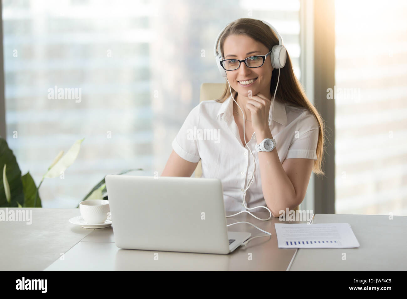 Smiling businesswoman wearing headphones with laptop posing at w - Stock Image