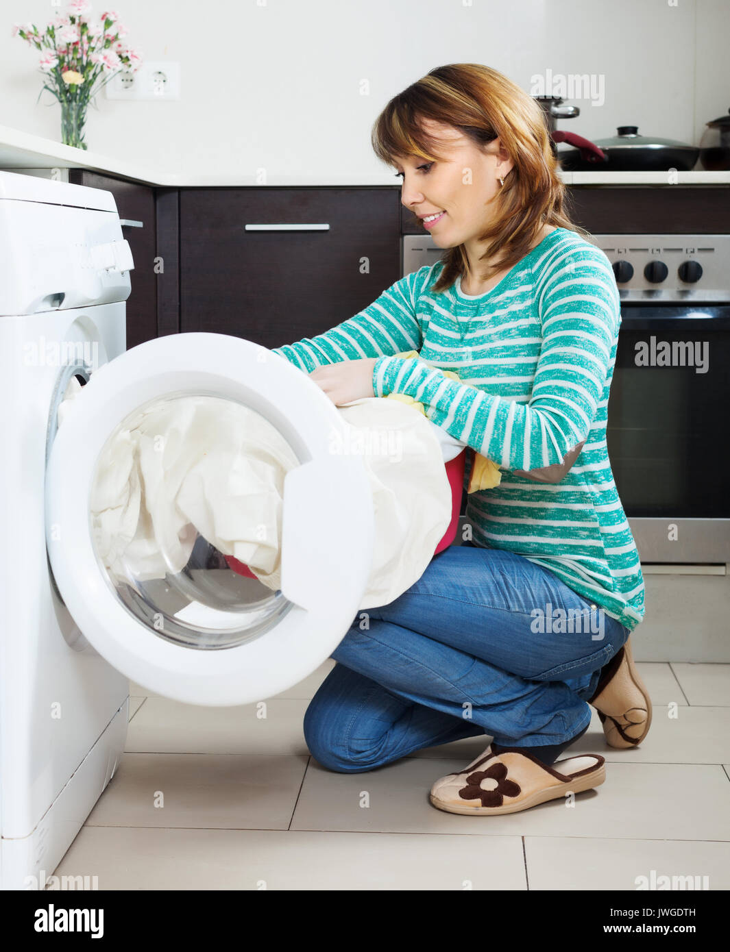 woman doing laundry with washing machine at home kitchen Stock Photo ...