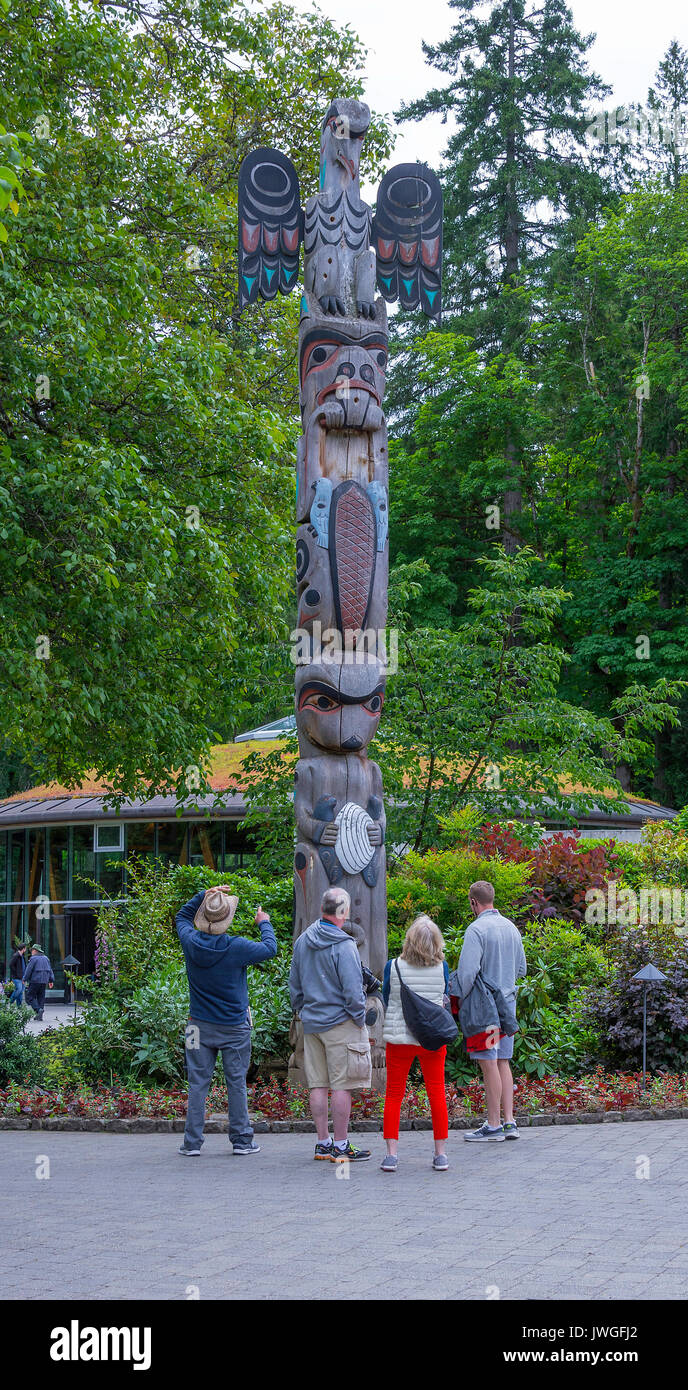 Visitors Admiring a Totem Pole Situated in The Butchart Gardens Victoria Vancouver Island British Columbia Canada - Stock Image