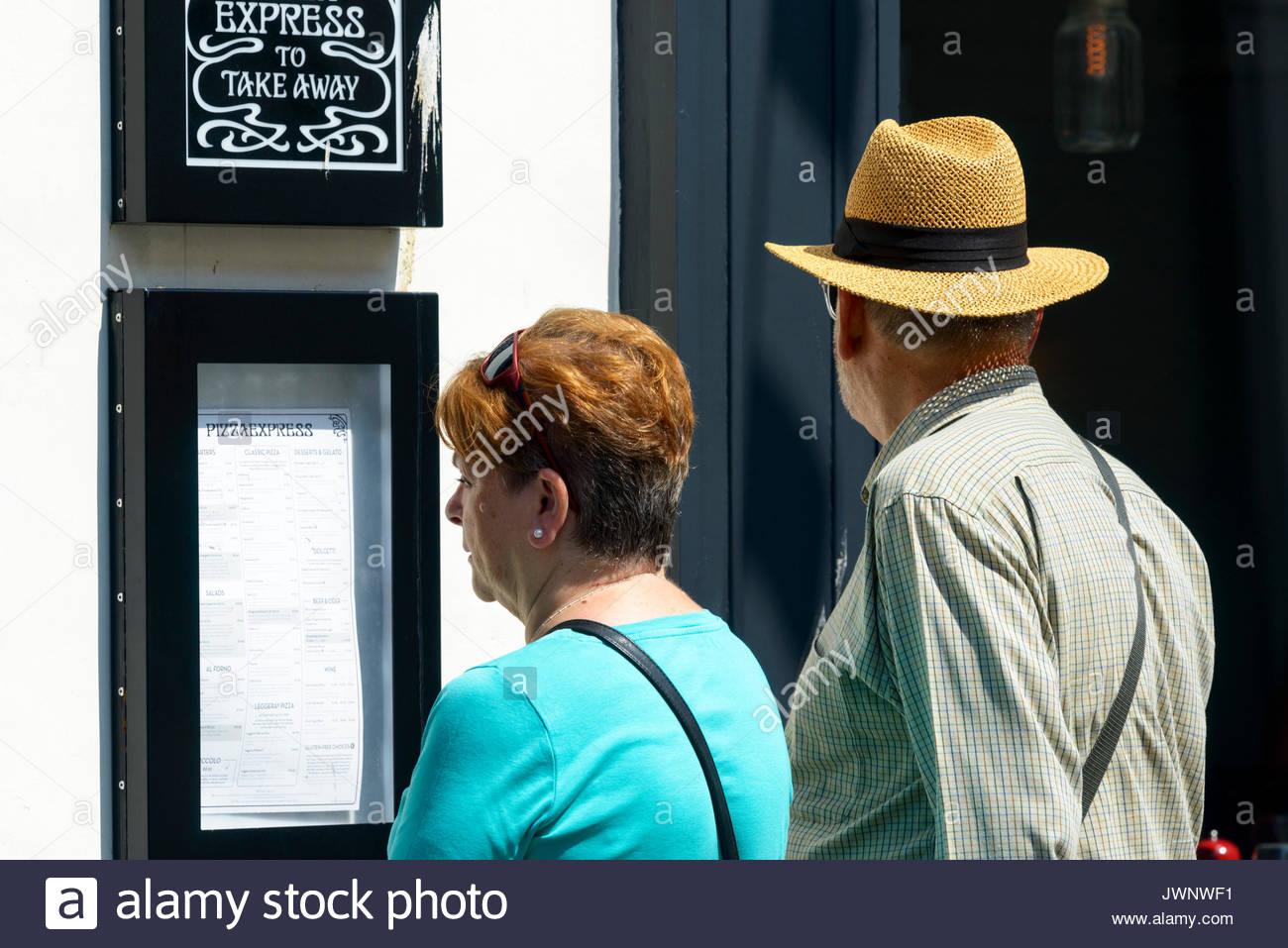 Couple reading restaurant menu, Poole, Dorset, England, UK - Stock Image