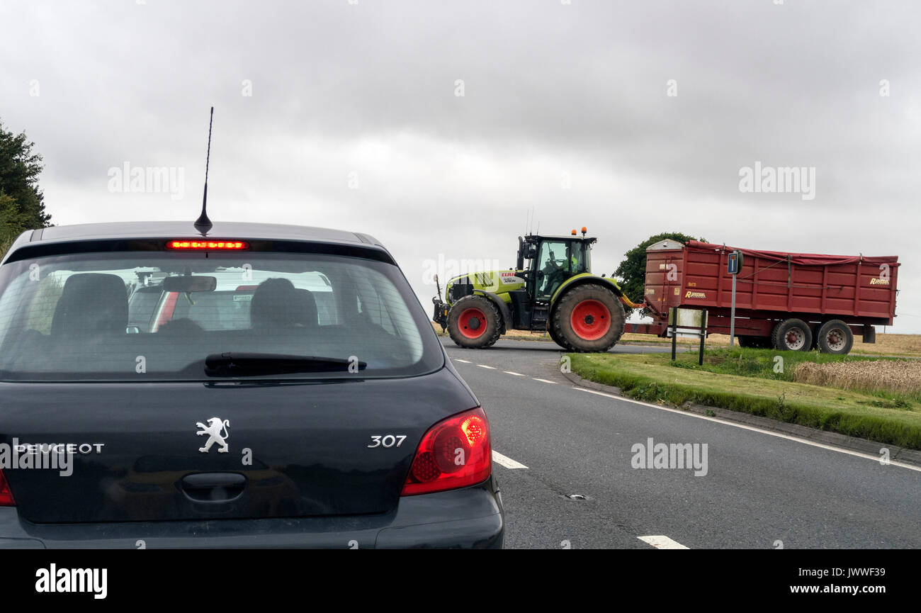 Traffic waits for an agricultural tractor to join the A303 trunk road in the South West of England. - Stock Image
