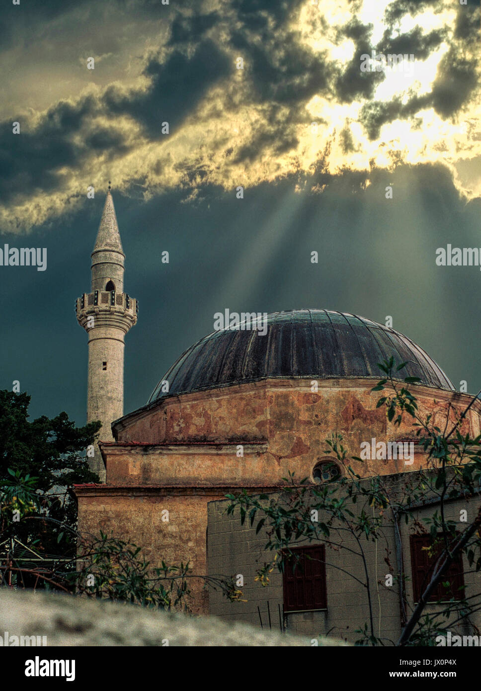 Old Mosque with Minaret in the Turkish section of Rhodes, Greece. the rays of the sun through the clounds seem to - Stock Image