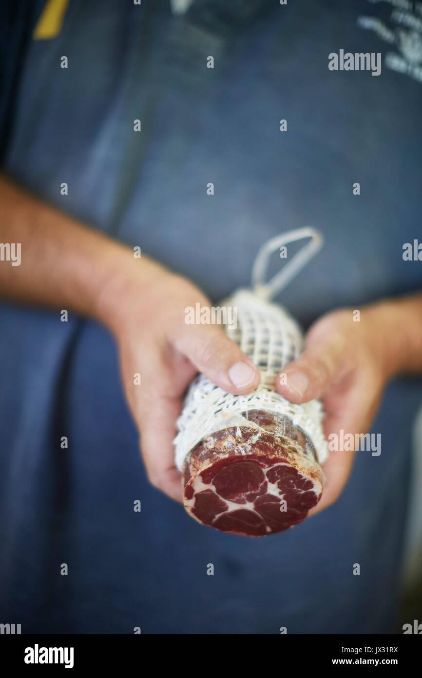 Man holding large salami - Stock Image