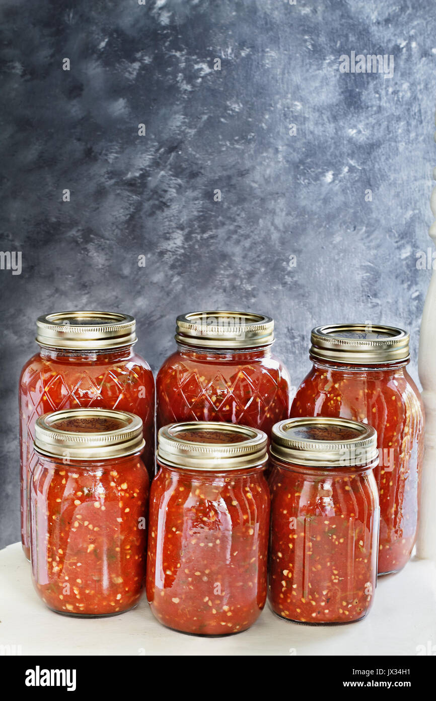 Mason jars canned with homemade salsa sitting on an old white country chair in front of a dark background. Shallow - Stock Image