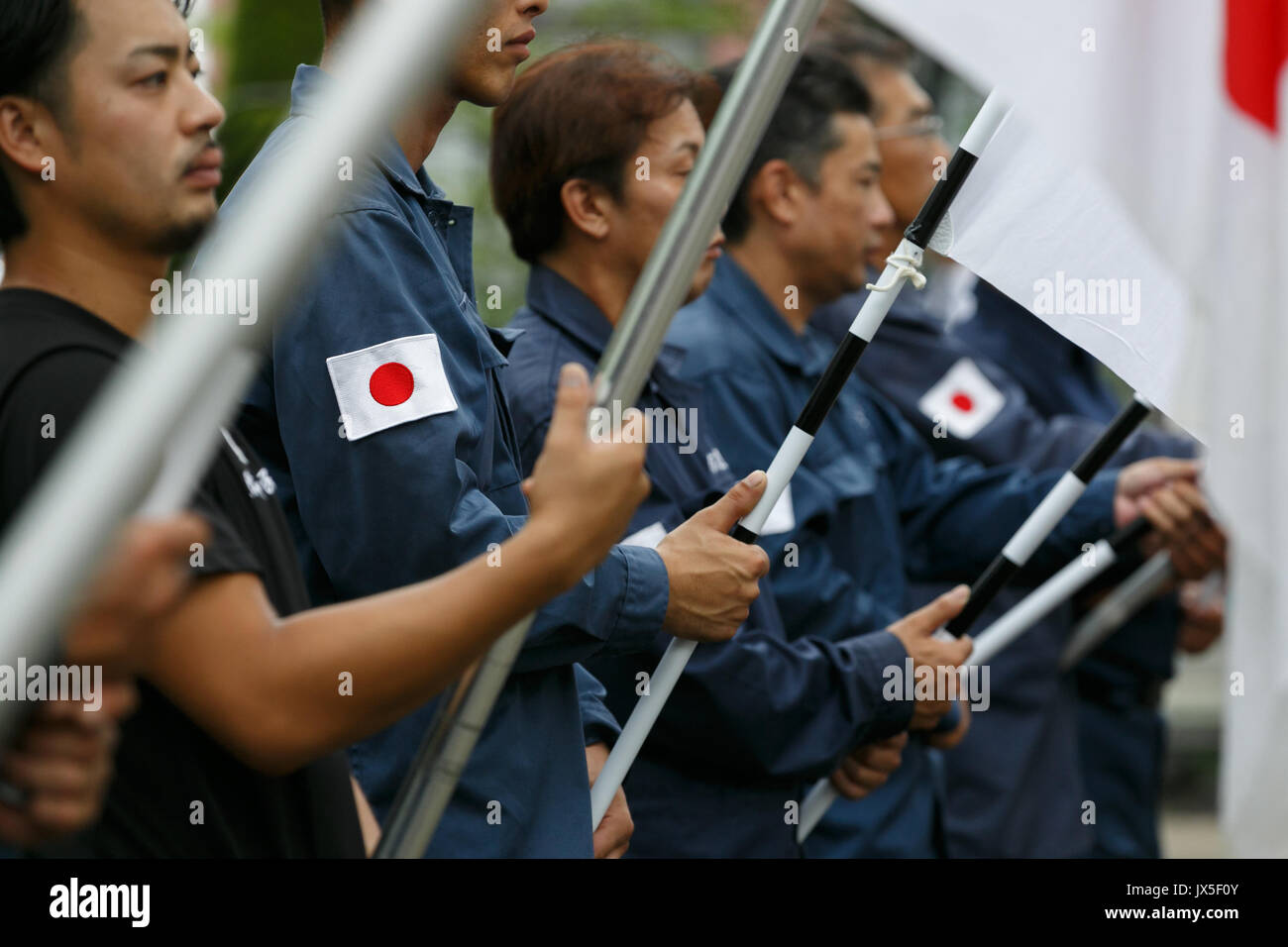 Tokyo, Japan. 15th Aug, 2017. Japanese nationalists dressed in military uniform hold war flags of the Imperial Japanese - Stock Image