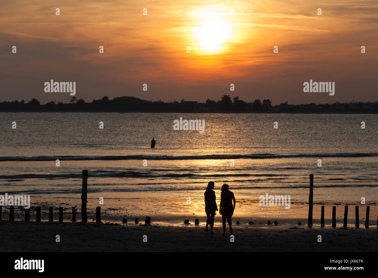 sunset-at-east-head-with-two-women-on-the-beach-west-wittering-west-JX66TK.jpg