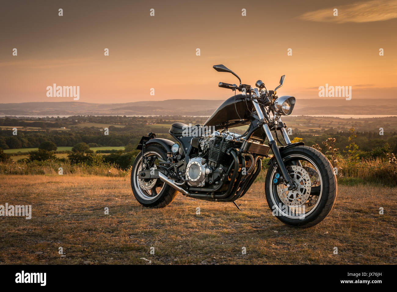 Custom made motorcycle parked during a quiet summer evening sunset. Stock Photo