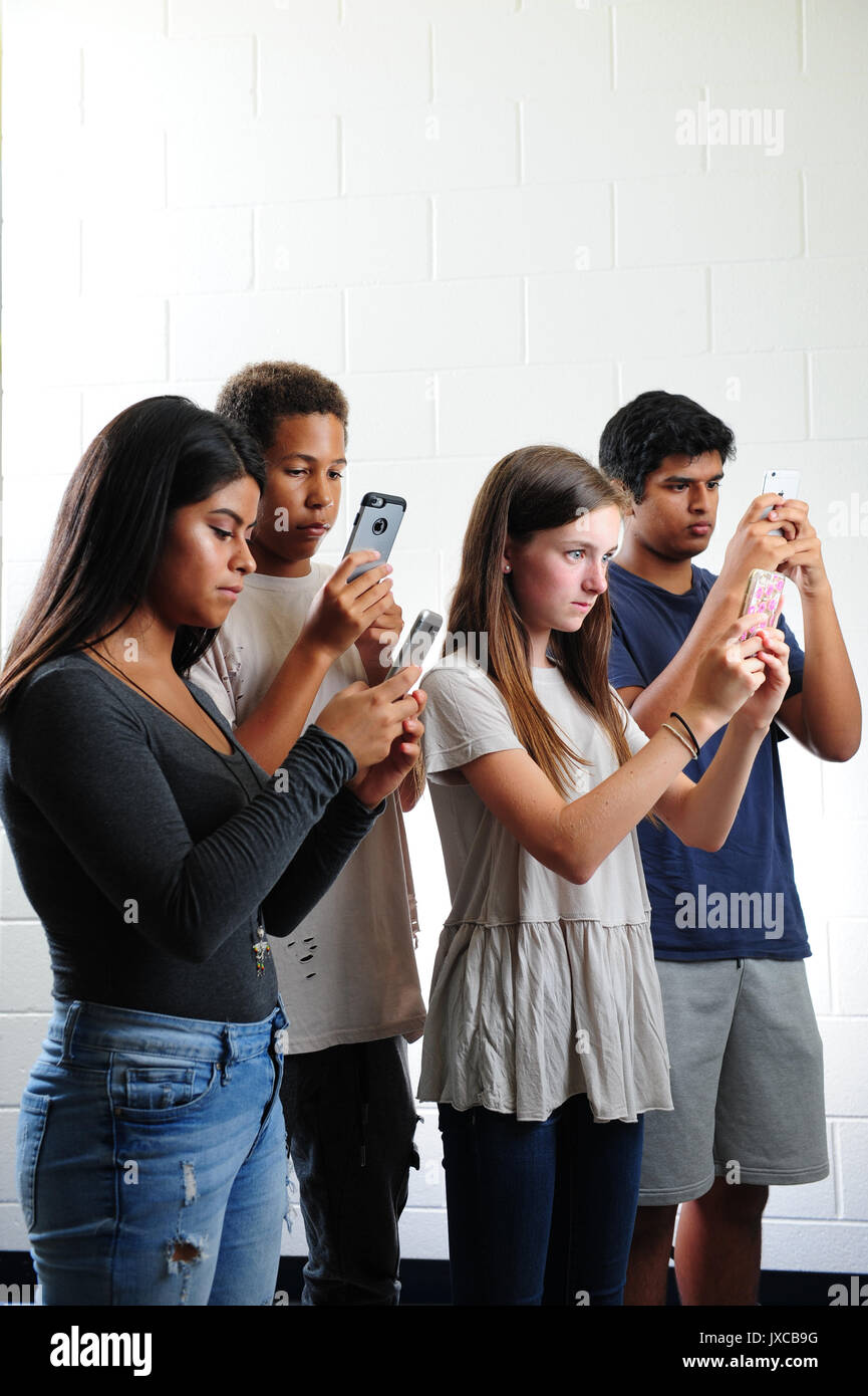 Teens kids addicted to and staring at their phones Stock Photo