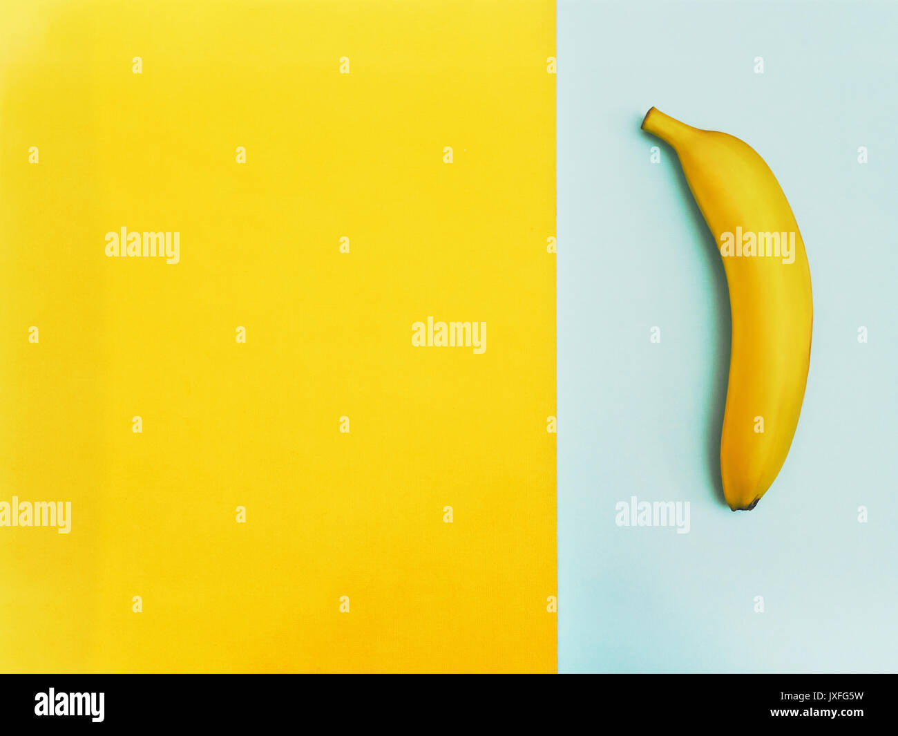 Fruit in flat lay Ripe yellow banana is lying on two-tone background Top view Trendy colorful flat lay photo of - Stock Image