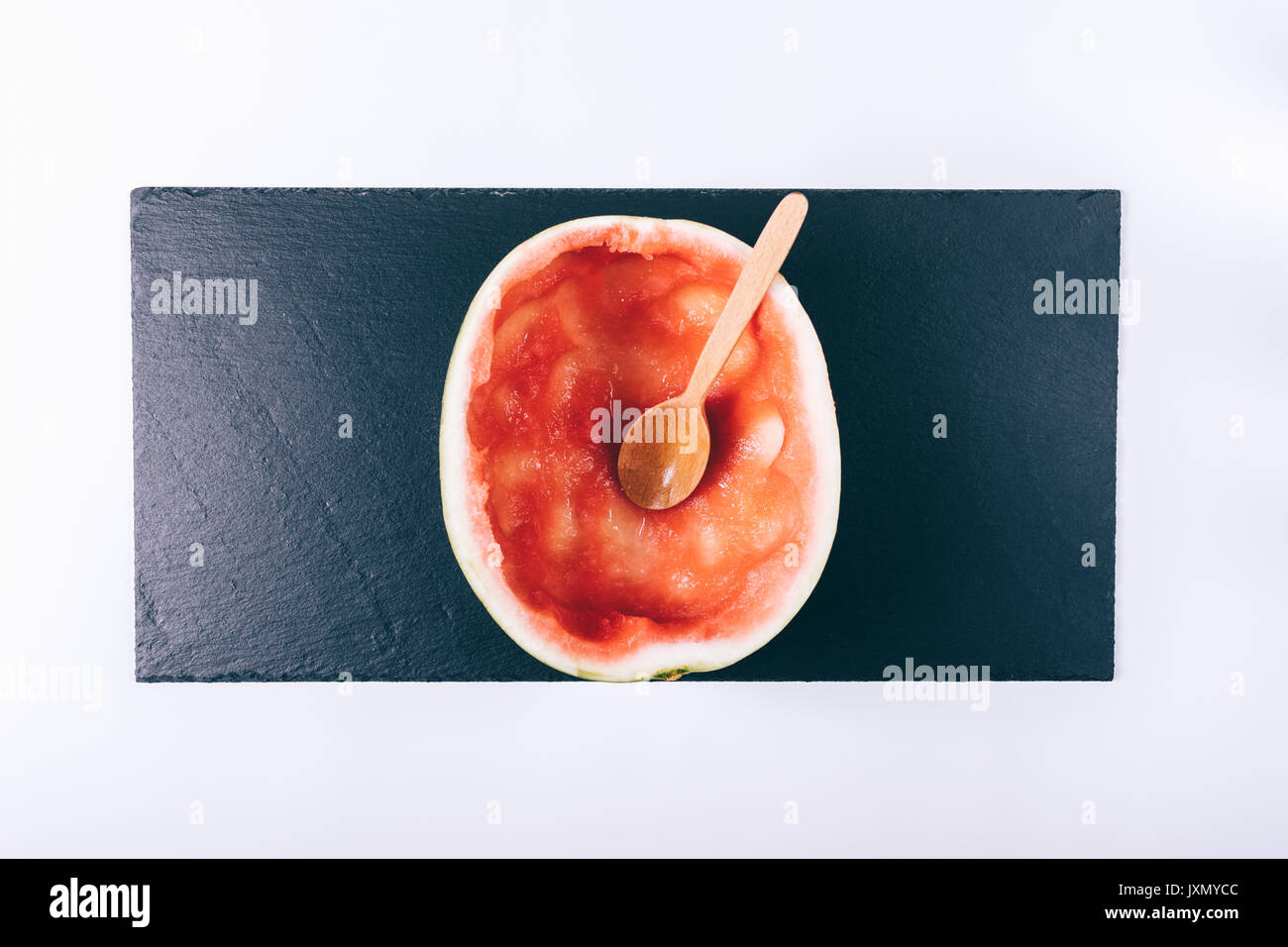 Eaten watermelon on a white table and wooden spoon top view - Stock Image