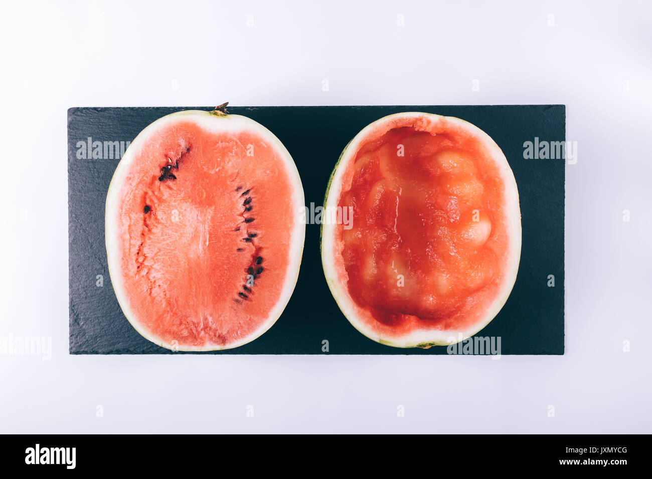 Sliced ripe watermelon on a white table top view - Stock Image