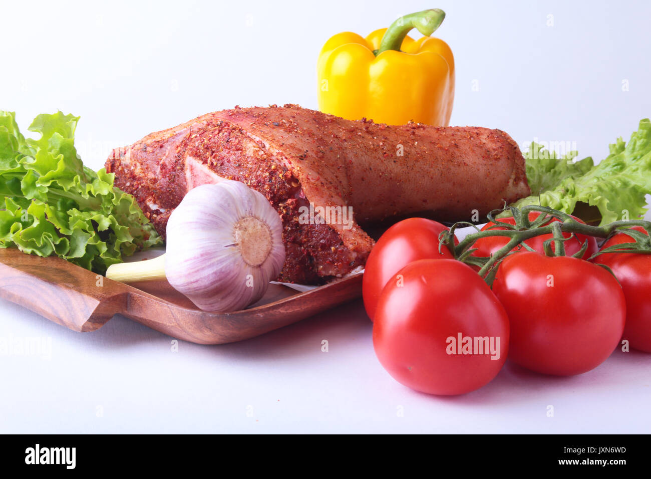 Raw pork knuckle and vegetables, garlic, tomatoes, bell pepper. spices and lettuce leaves on a cutting board. Selective - Stock Image