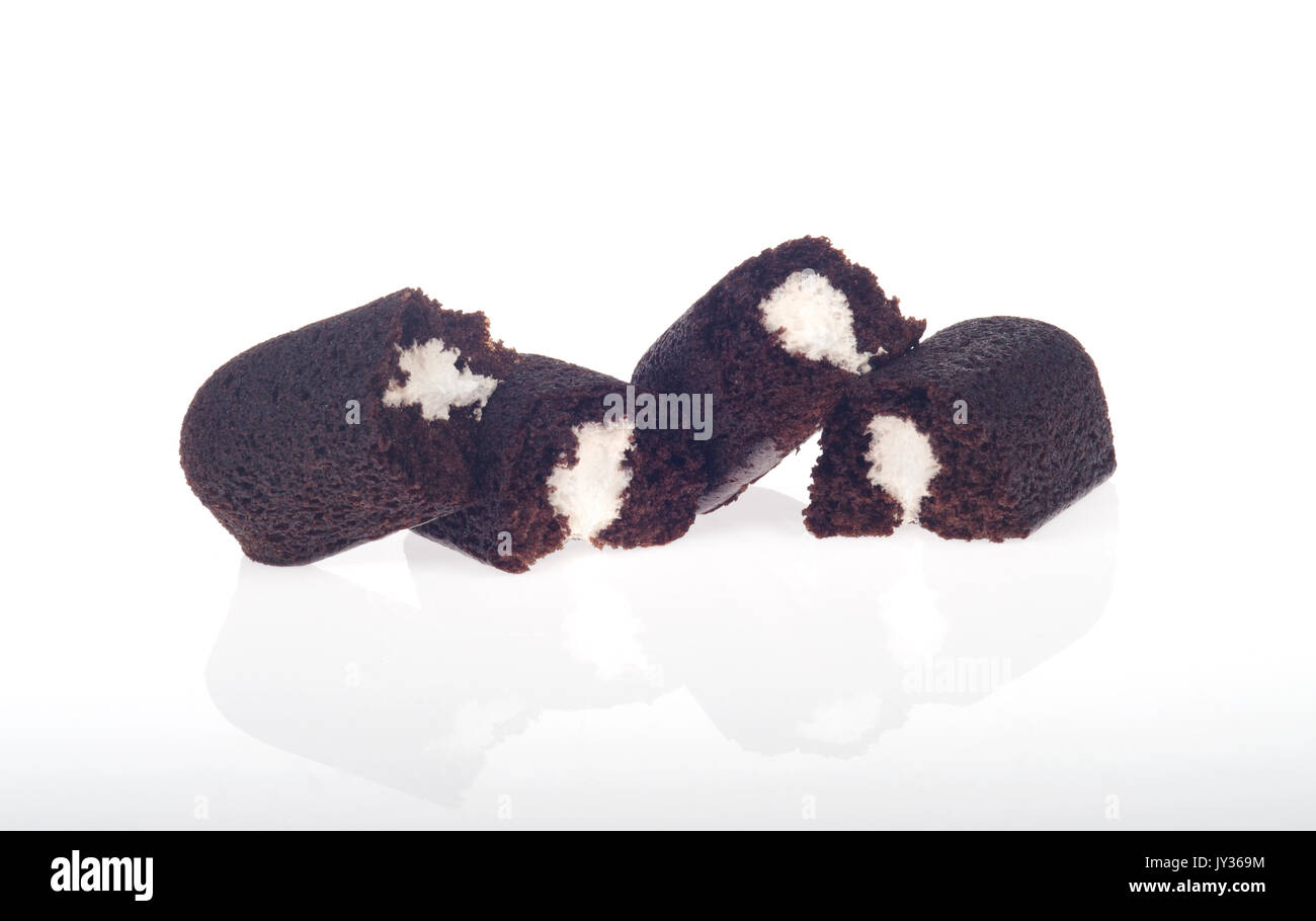 Chocolate Hostess Twinkies  cut in half with vanilla cream filling visible  on white background, isolate. USA - Stock Image