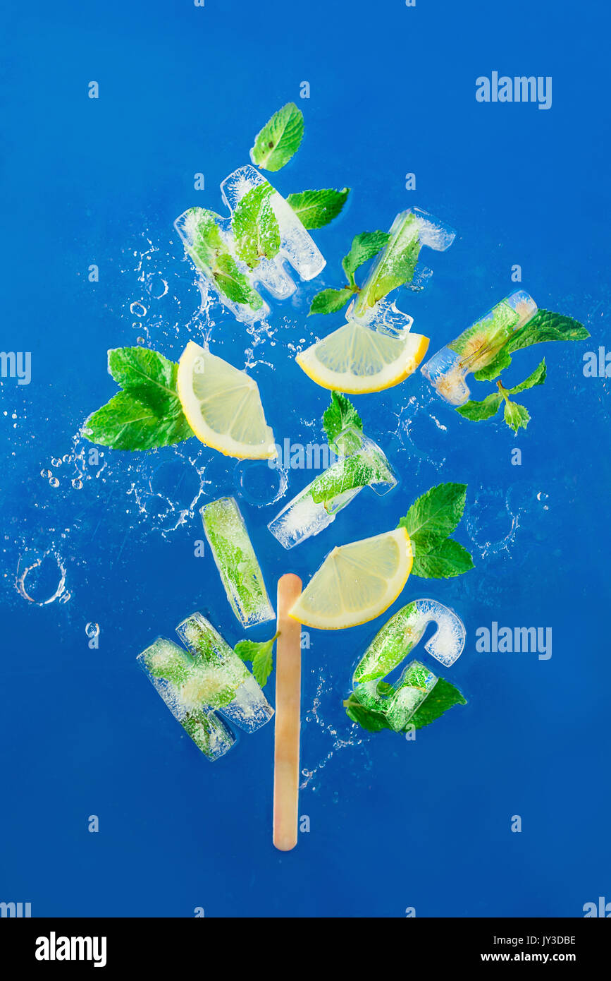 Ice cube lettering with frozen mint leaves, lemon slices and oranges on a blue background with water splashes. Text - Stock Image