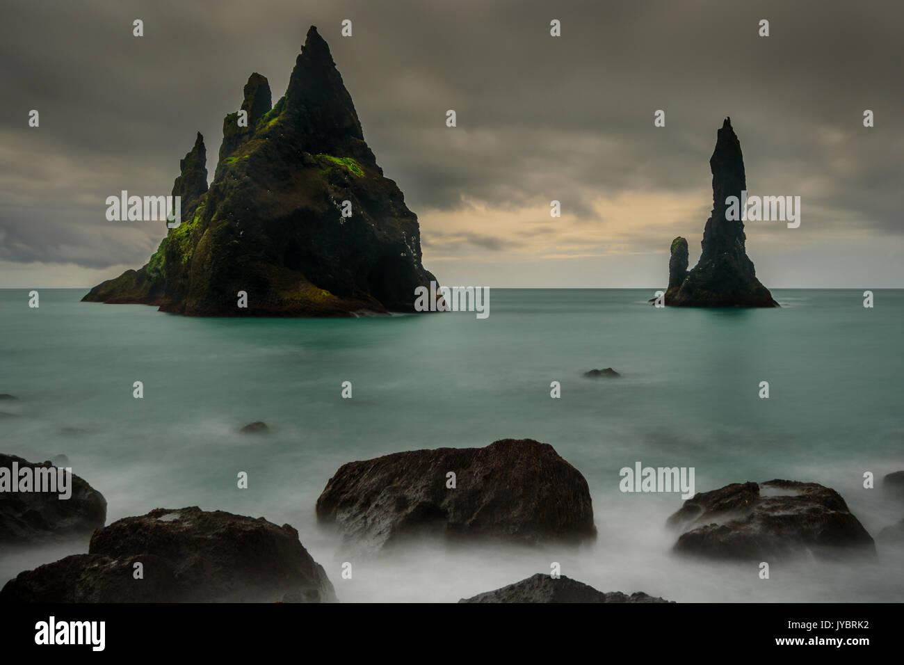 Basalt stacks of Reynisdrangar in a dark mood. - Stock Image