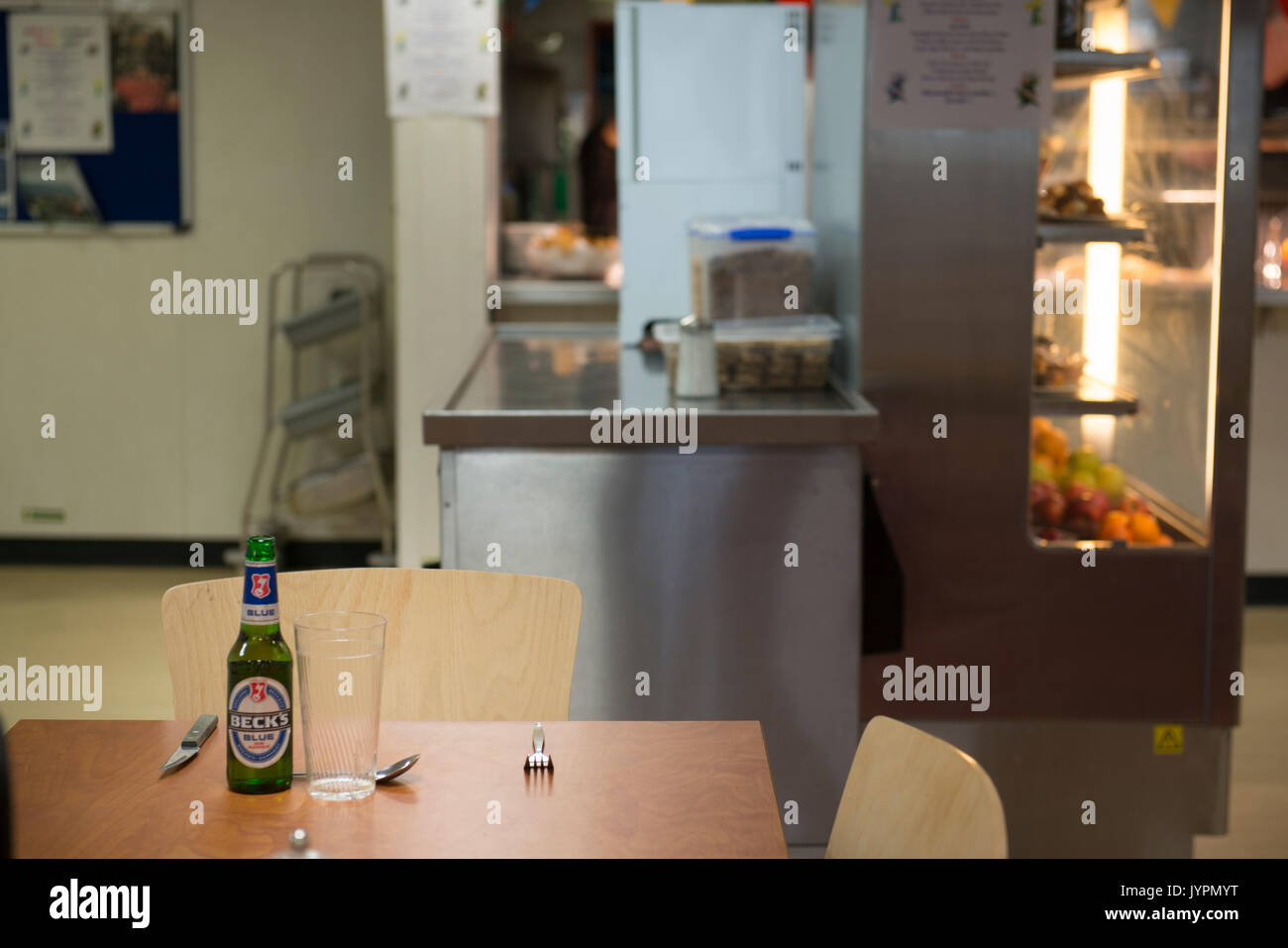 A dinner place setting, with a bottle of backs blue non-alcoholic larger. On an oil and gas rig, in the North Sea. - Stock Image