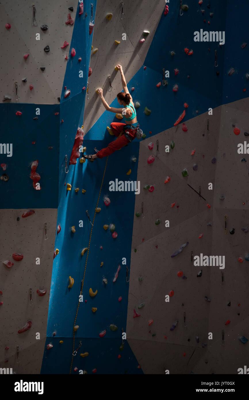 Young woman climbing at indoor wall. Europe. - Stock Image