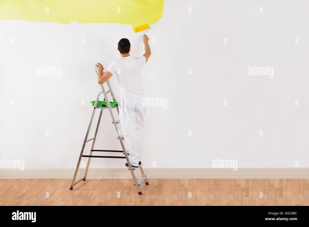 Rear view of young man painting wall with yellow paint roller at home - Stock Image