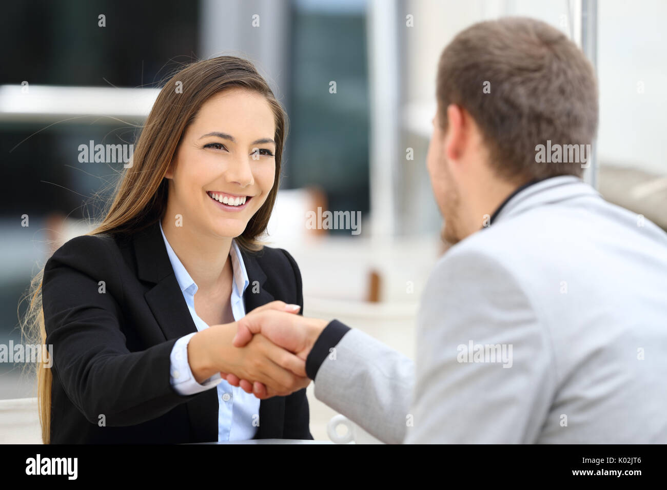 Two executives meeting and handshaking sitting in a coffee shop Stock Photo