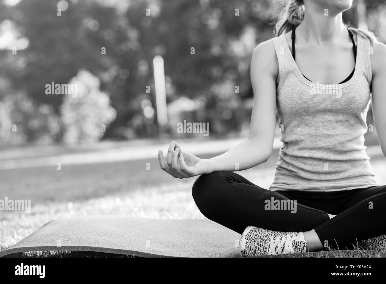 Young woman practicing yoga outdoors at the park - Stock Image