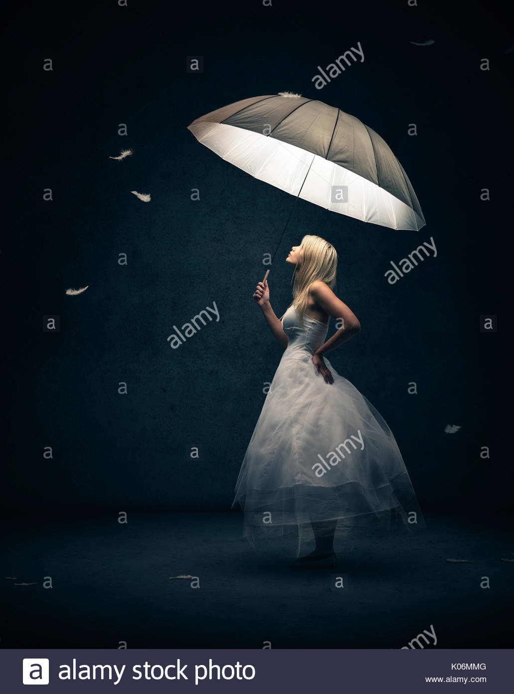 Girl dressed in white with light emitting umbrella looking up at falling feathers - Stock Image