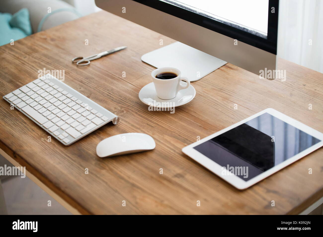 Picture of computer, scissors and camera on working desk - Stock Image