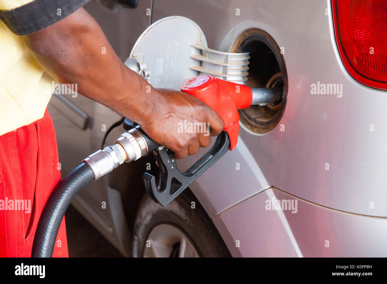 Car refueling at the petrol station. Image concept for use of fossil fuels (gasoline, diesel) in combustion engines - Stock Image