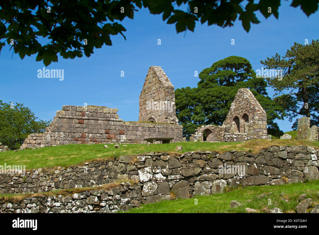 Ruins of historic 13th century Saint Blane's church and monastery against blue sky on island of Bute, Scotland - Stock Image