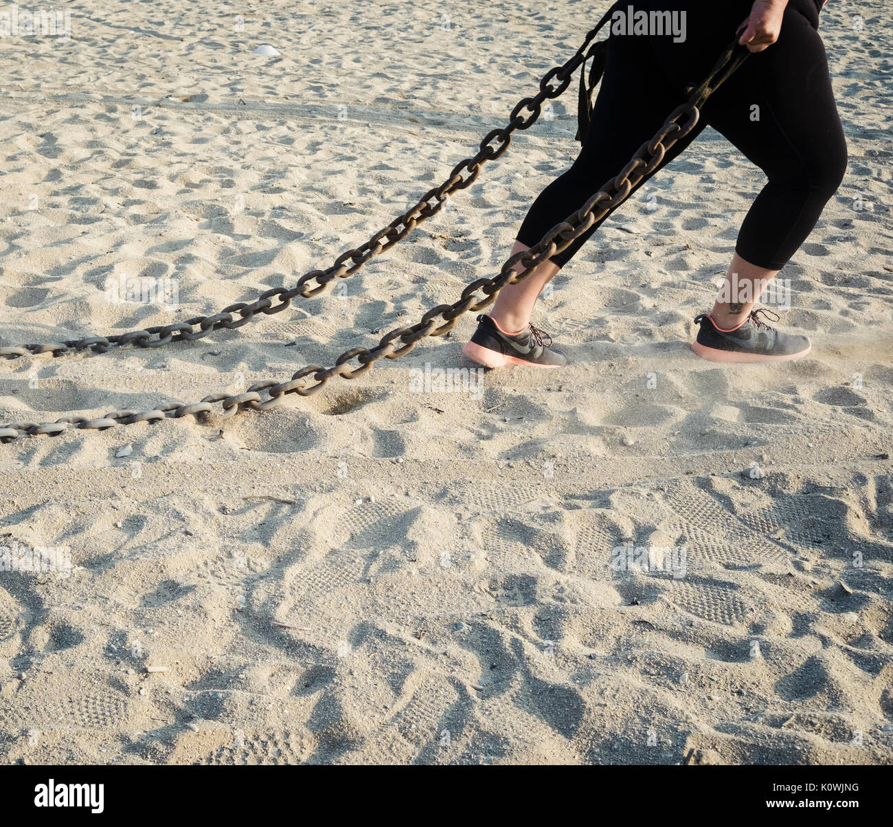 A woman drags a metal chain as part of a bootcamp fitness session on Falmouth's Gyllyngvase Beach. Stock Photo