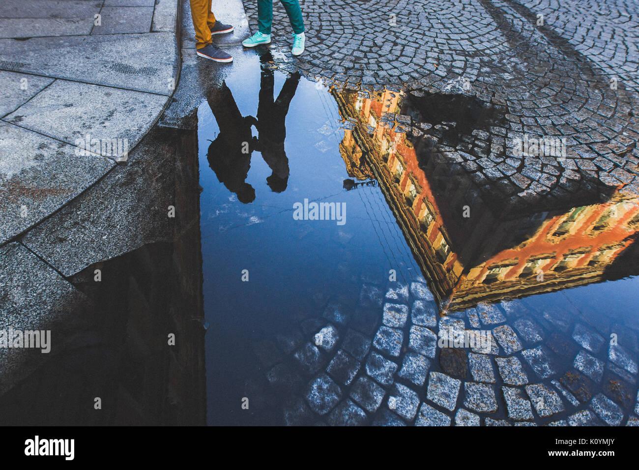 Silhouette hugging guy and girl in reflection in puddle on a street. Saint-Petersburg Love - Stock Image