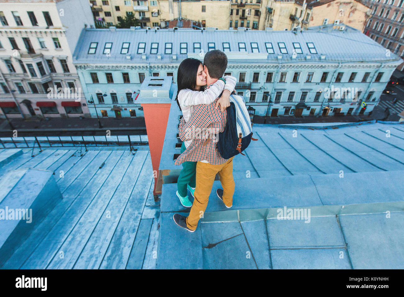 Young happy couple walking on the roofs of St. Petersburg. Beautiful view of the city from above. Casual style - Stock Image