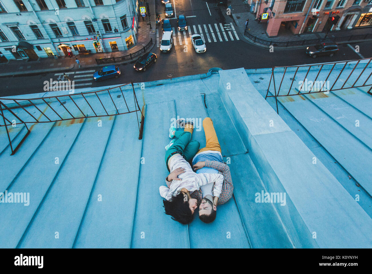 Young hipster couple lying on the roof and kissing. Beautiful view of the city from above. Casual style - Stock Image