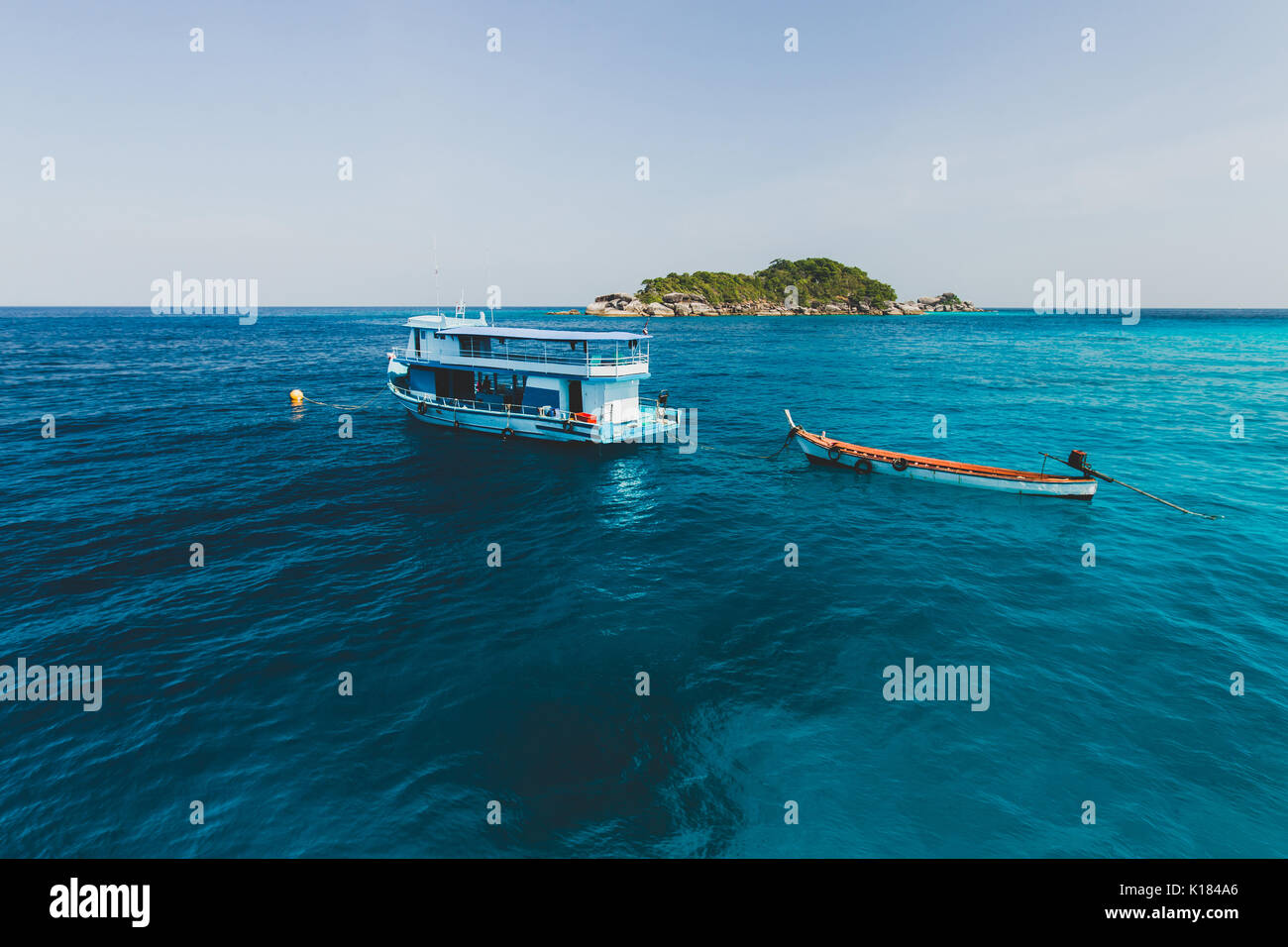 Tourist boat near island shore with turquoise clear transparent water. Idyllic view of Similan Islands - Stock Image