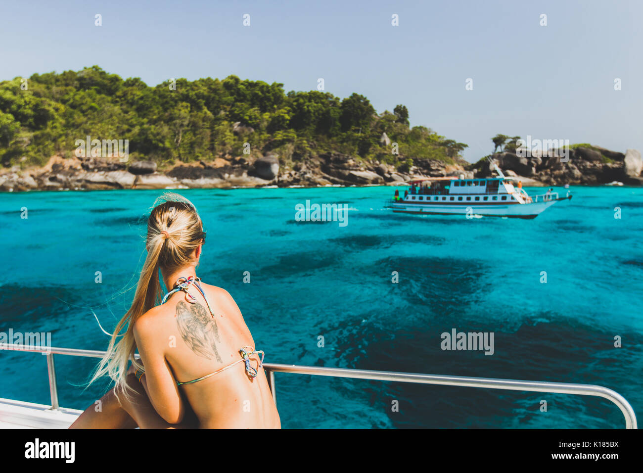 Blonde woman with tattoo on back relaxing on luxury yacht with view of paradise tropical island with turquoise water - Stock Image