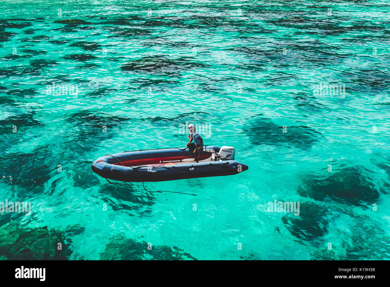 SIMILAN, THAILAND- JANUARY 31, 2014: Inflatable boat floats on surface of the pure clear water at bay of tropical - Stock Image