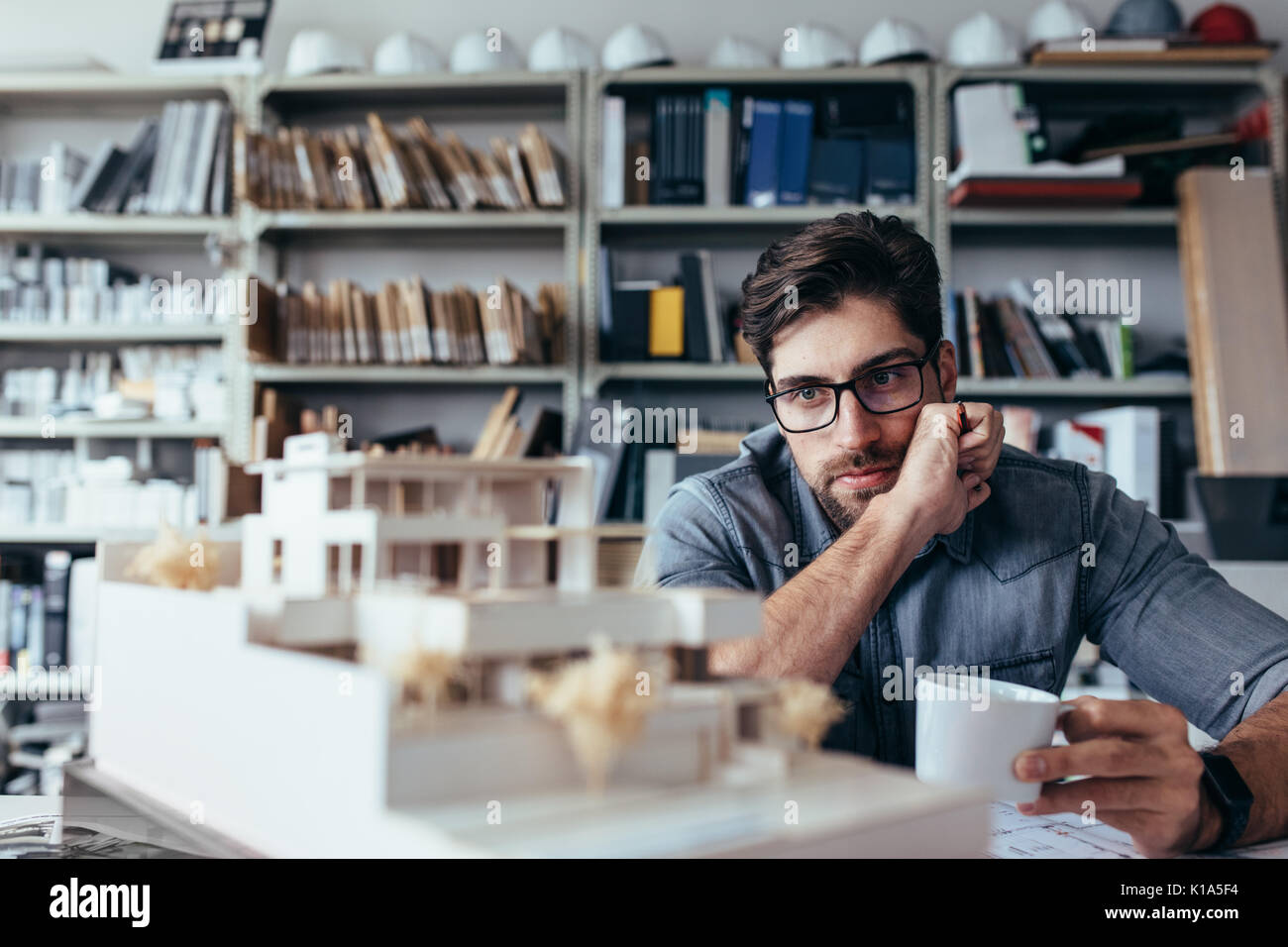 Thoughtful male designer in office looking at model with cup of coffee. Young male architect taking break from work. - Stock Image