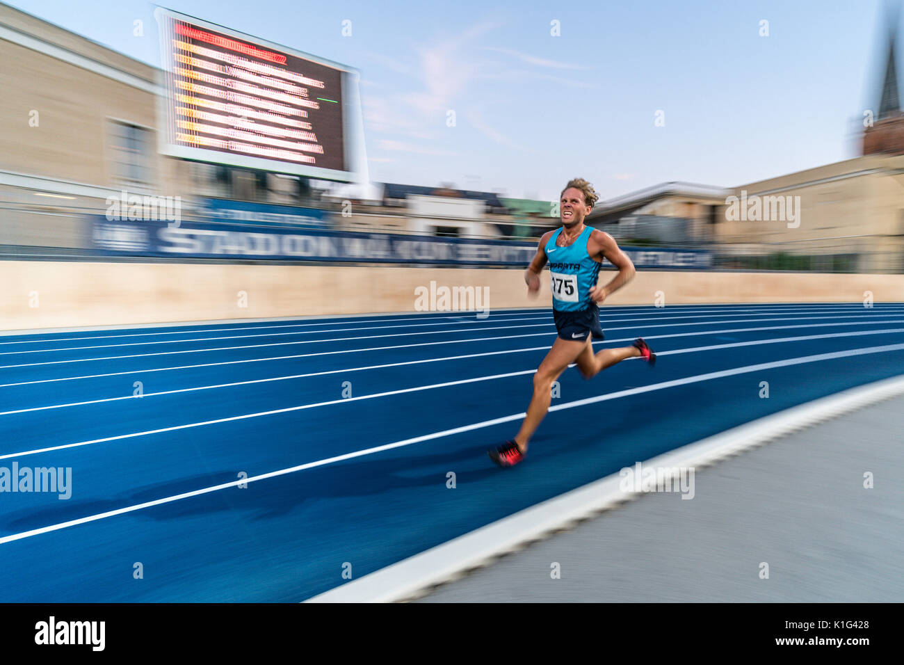 Panning shot of running on the final lap of 5 k track race - Stock Image