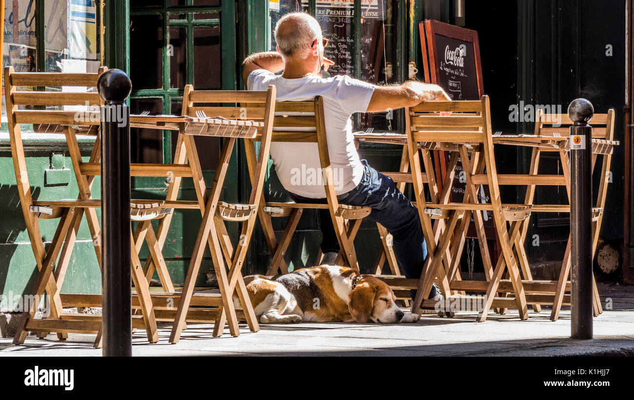 Cafe/bar owner sitting outside in the warm September sunshine among table and chairs, with his dog asleep on the Stock Photo