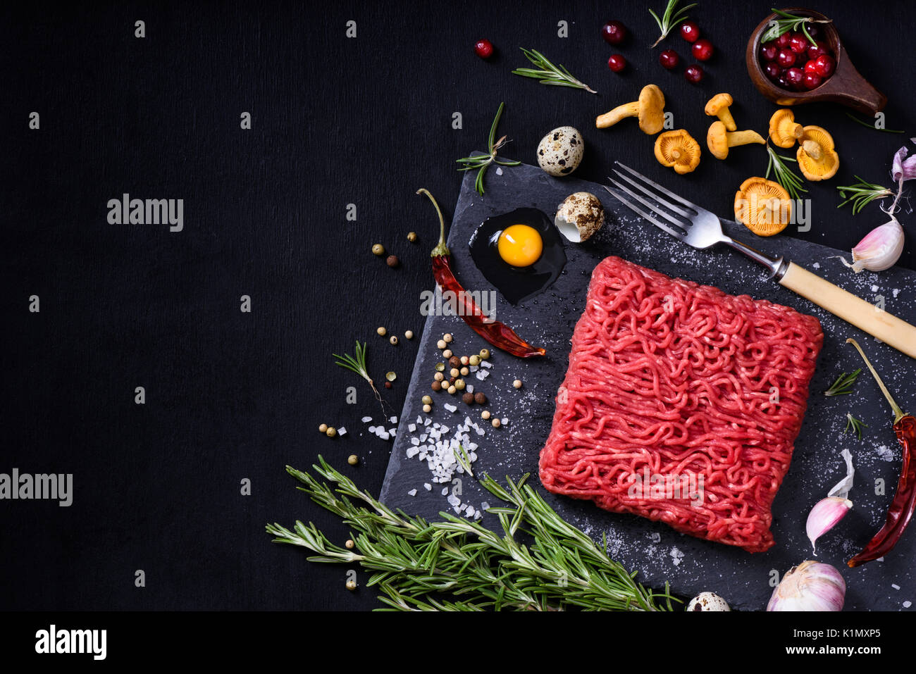 Tasty raw veal or beef meat on black table. Cooking ingredients with ground meat. Top view, copy space. - Stock Image