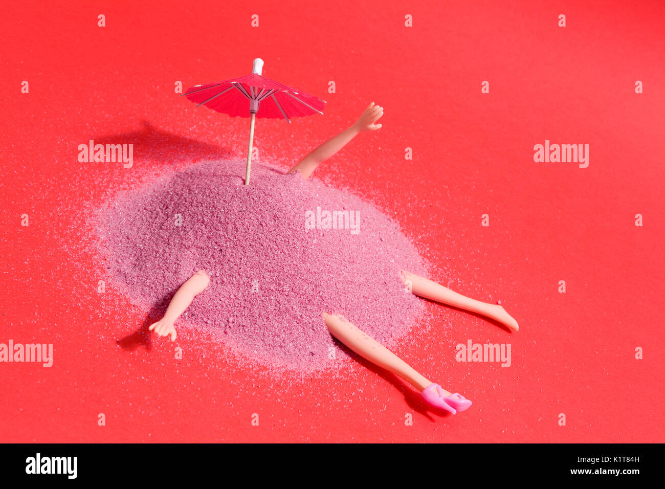 Arm and leg's doll emerging from a pile of pink sand as if it were hiding. Minimal funny and quirky design still - Stock Image
