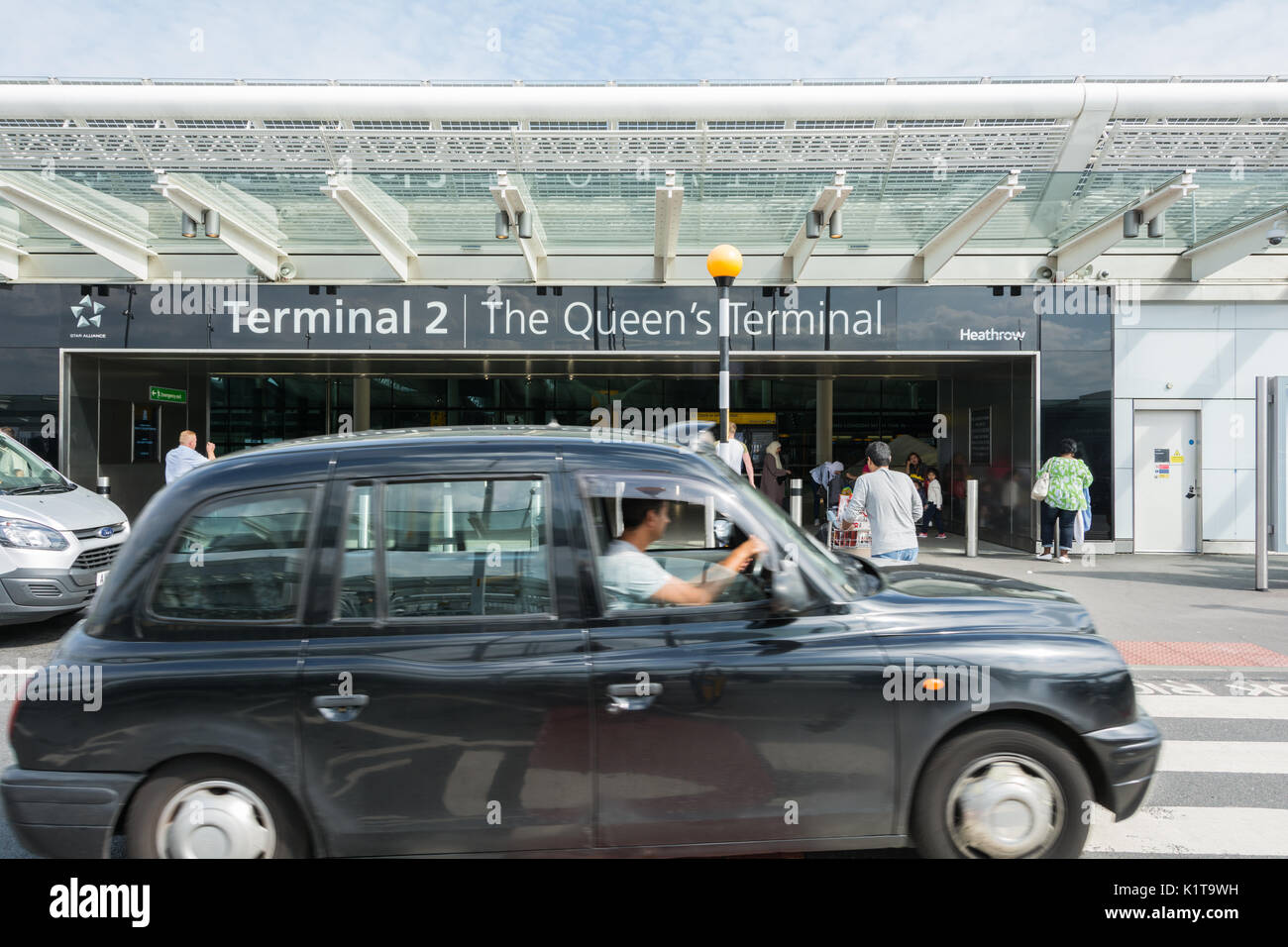 A black taxi cab outside Heathrow Airport Terminal Two Building, The Queens Terminal, London, UK Stock Photo