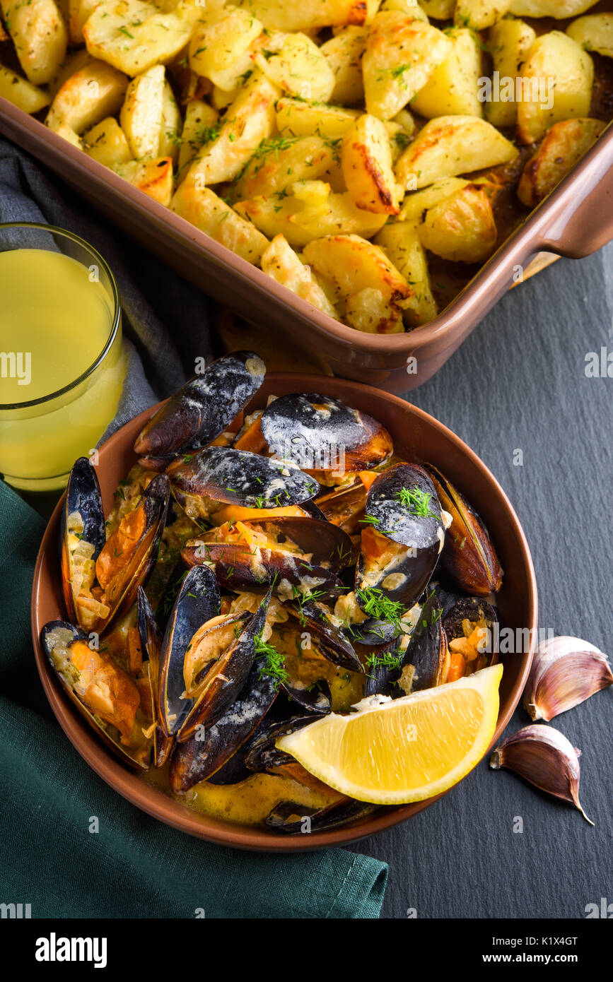 Shellfish mussels in bowl served with baked potato with celery, garlic and lemon. High view angle view - Stock Image