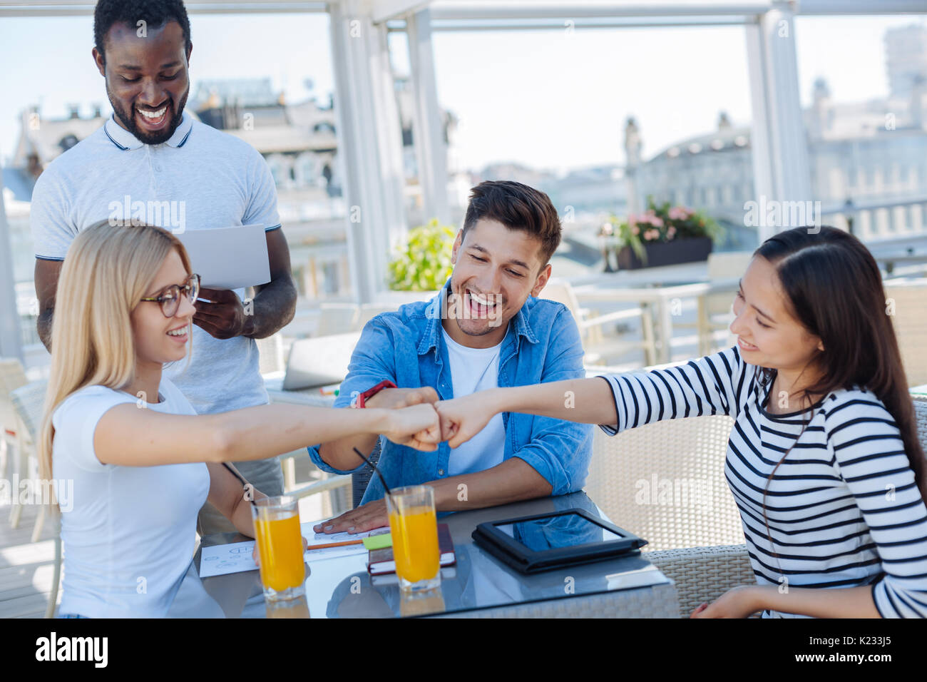 Cheerful company of young people joining fists together - Stock Image