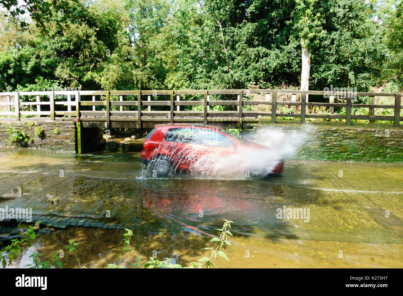 Car driving at speed through the ford at Rufford, Nottinghamshire. - Stock Image