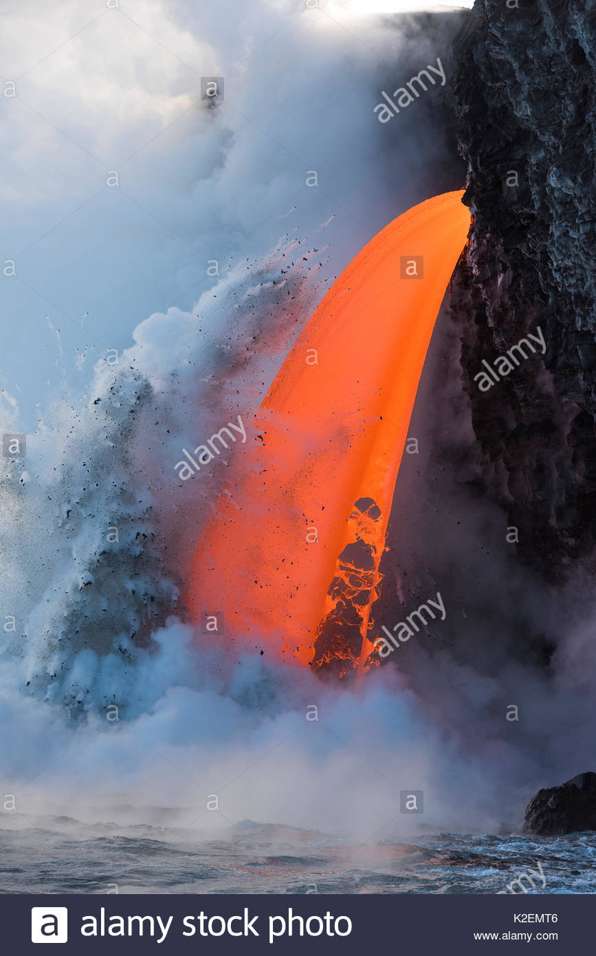 Hot lava from the 61G flow from Kilauea Volcano entering the ocean from the open end of a lava tube at the Kamokuna - Stock Image