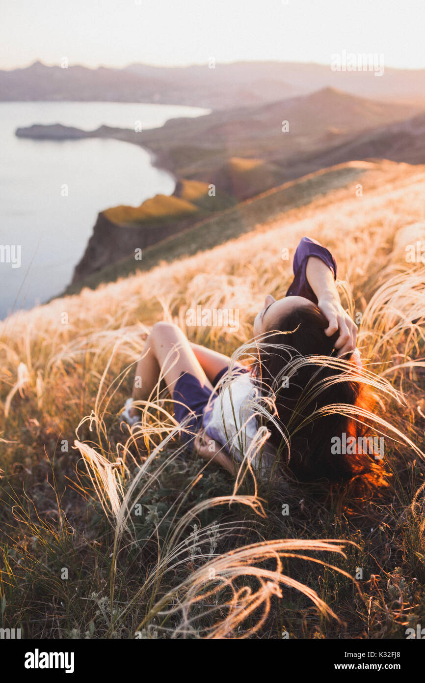 Young woman relaxing in feather grass field at sunset. Enjoying beautiful mountain view and sea coast in Koktebel - Stock Image