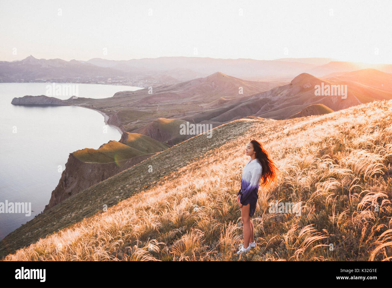 Young girl walking at nature and enjoying  view of the coast, field of feather grass and setting sun. White-blue - Stock Image
