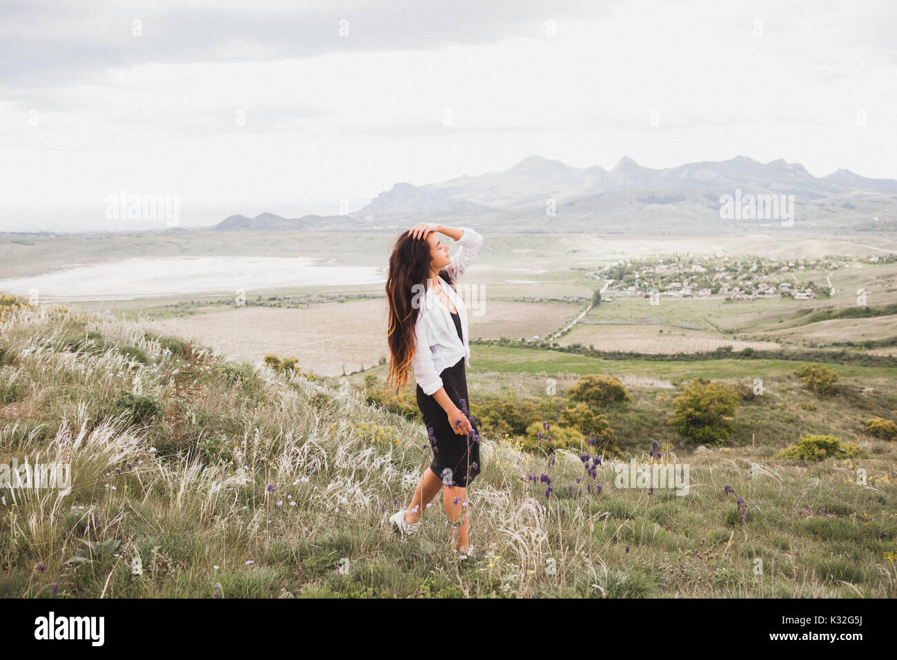 Young girl walking at nature and enjoying  mountain view, field of feather grass and green valley. White-black style - Stock Image