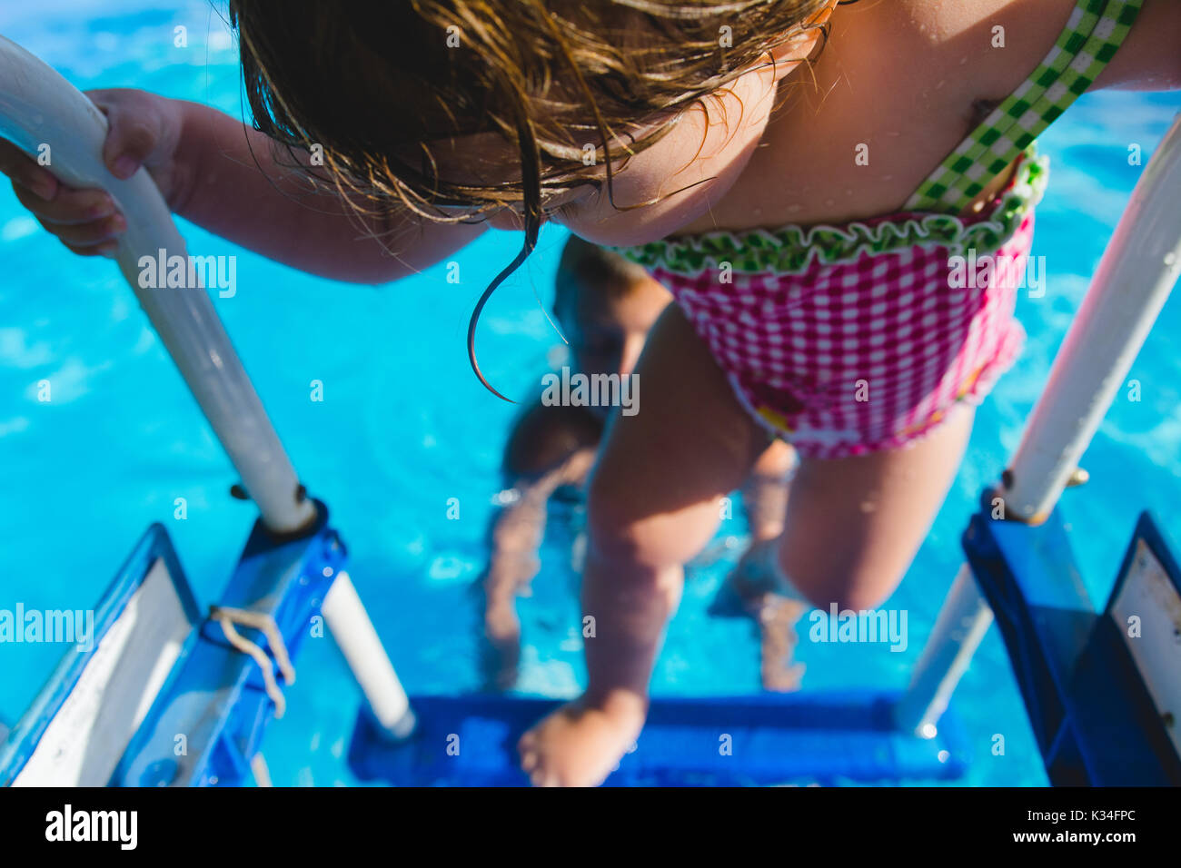 A young girl climbs out of a swimming pool during  the summer. - Stock Image